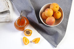 The Apricots in a bowl and jam in a jar on a white table with a red and white towel. handmade summer blanks Royalty Free Stock Image