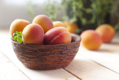 Apricots in ceramic cup on wooden table. selective focus Royalty Free Stock Images