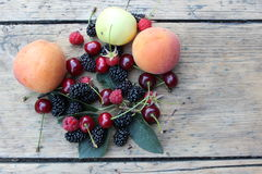 Apricots, cherries, mulberries and raspberries on the boards. Various summer fruits lying on wooden boards Stock Photography