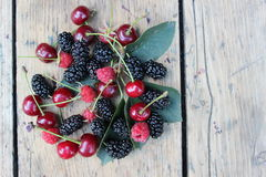 Apricots, cherries, mulberries and raspberries on the boards. Various summer fruits lying on wooden boards Stock Photos