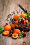 Apricots and cherries on rustic  background Royalty Free Stock Photo