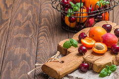 Apricots and cherries on rustic  background Stock Photo