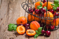Apricots and cherries on rustic  background Royalty Free Stock Photos
