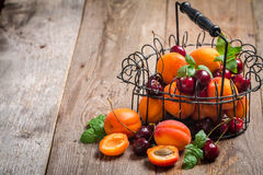 Apricots and cherries on rustic  background Royalty Free Stock Images