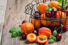 Apricots and cherries on rustic  background Royalty Free Stock Image