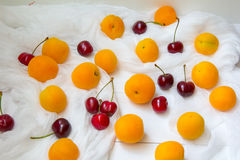 Apricots and cherry berries at white background Royalty Free Stock Image
