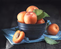 Apricots. Closeup of fresh organic apricot fruits in a bowl. On dark rustic wooden table royalty free stock photography