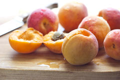 Apricots on cutting board. Freshly washed apricots on wooden cutting board with knife Royalty Free Stock Images