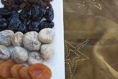 Apricots, figs and raisins with gold tablecloth at Christmas Royalty Free Stock Images