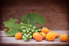 Apricots and grapes on a wooden table Royalty Free Stock Photo