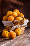 Apricots group in knitted basket. On old rustic wooden table and dark background Stock Photo