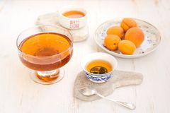 Apricots, honey and tea on a white background. With silver spoon Royalty Free Stock Photography