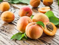 Apricots and its cross-section on the old wood. En table royalty free stock photography