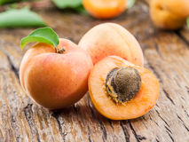 Apricots and its cross-section on the old wood. Royalty Free Stock Photography