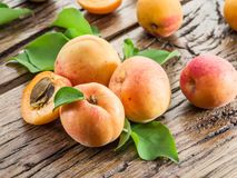 Apricots and its cross-section on a old wooden table. Royalty Free Stock Photos