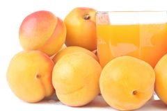 Apricots juice. Glass of freshly squeezed juice and ripe bright apricots isolated on white background Stock Images