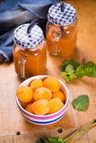Apricots with juice. Some fresh ripe raw apricots with juice on wooden background Stock Photos