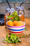 Apricots with juice. Some fresh ripe raw apricots with juice on wooden background Stock Images