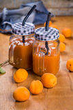 Apricots with juice. Some fresh ripe raw apricots with juice on wooden background Royalty Free Stock Image
