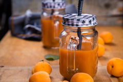 Apricots with juice. Some fresh ripe raw apricots with juice on wooden background Stock Photo