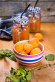 Apricots with juice. Some fresh ripe raw apricots with juice on wooden background Royalty Free Stock Photo