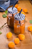 Apricots with juice. Some fresh ripe raw apricots with juice on wooden background Stock Image