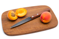 Apricots and a knife on a wooden cutting board Royalty Free Stock Image