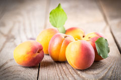 Apricots with leaves. On the old wooden table royalty free stock photo