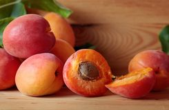 Apricots with leaves on a wooden table. Royalty Free Stock Photography