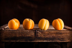 Apricots lined on old wooden box. Apricots group lined up on top rustic wooden box and dark background Royalty Free Stock Photo