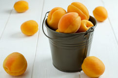 Apricots. In metal pail on a wooden white table royalty free stock photos