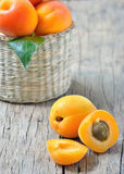 Apricots on the old wooden table and basket shoot in studio Royalty Free Stock Images