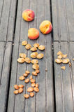 Apricots and pits on a wooden table Royalty Free Stock Images