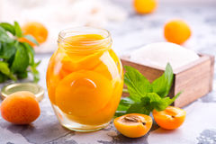 Apricots. With sirup in glass bank and on a table Royalty Free Stock Photography