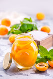 Apricots. With sirup in glass bank and on a table Stock Photos