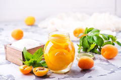 Apricots. With sirup in glass bank and on a table Royalty Free Stock Photos
