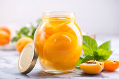 Apricots. With sirup in glass bank and on a table Royalty Free Stock Images