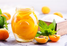 Apricots. With sirup in glass bank and on a table Royalty Free Stock Image