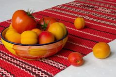 Apricots and tomatoes in a bowl on the red embroidered cloth Royalty Free Stock Photos
