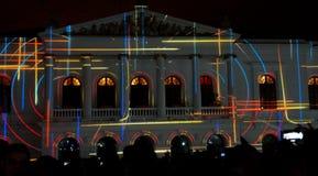 Apriete admirando el espectáculo de las luces proyectadas en la fachada del Teatro Sucre, en el centro histórico de Quito Fotos de archivo libres de regalías