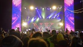 Apriete a la gente con los teléfonos móviles en las manos disfrutan de música en directo en el partido del concierto en reflector almacen de video