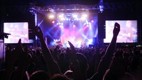 Apriete la palmada sus manos, iluminadas por la iluminación colorida durante concierto de rock de la noche, muchedumbre de la aud metrajes