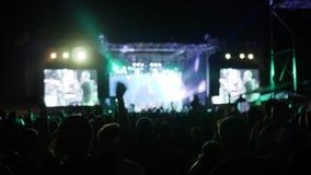 Apriete saltan y bailan en el festival de la roca, brazos aumentados de fans en las luces brillantes de la etapa, manos que agita metrajes
