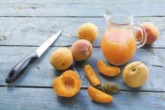 Aprikors, fruktsaft i en glass tillbringare och en kniv på ett gammalt blått trä Royaltyfri Fotografi