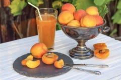 Aprikors i en metallvas och ett exponeringsglas av aprikosfruktsaft Arkivbilder