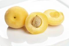 Aprikors och halvor på en platta Arkivfoton
