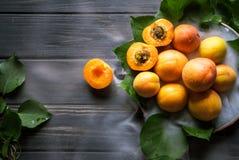 aprikors på en platta och en låg dimma på en svart träbakgrund arkivfoton