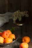 Aprikosen auf der Platte, weiße Blumen, hölzerner Hintergrund Lizenzfreie Stockfotografie