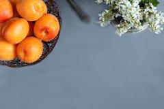 Aprikosen auf der Platte, weiße Blumen, konkreter Hintergrund Lizenzfreie Stockfotografie