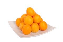 Aprikosen auf weißer Platte Stockbild